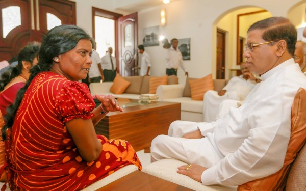 Sri Lankan President Maithripala Sirisena is listening and conversing with Vidhya Sivaloganathan's mother Saraswathi Sivaloganathan, during his special visit to Jaffna on May 26 to console the grieving family and assure justice.